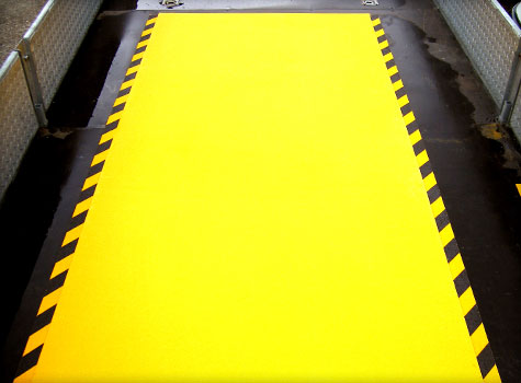 8. Anti-Slip Floor Sheets with hazard stripes for a vehicle loading area.
