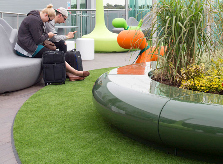 Curved planters and the natural greens were specified to help calm and help soften the airport space and architecture.
