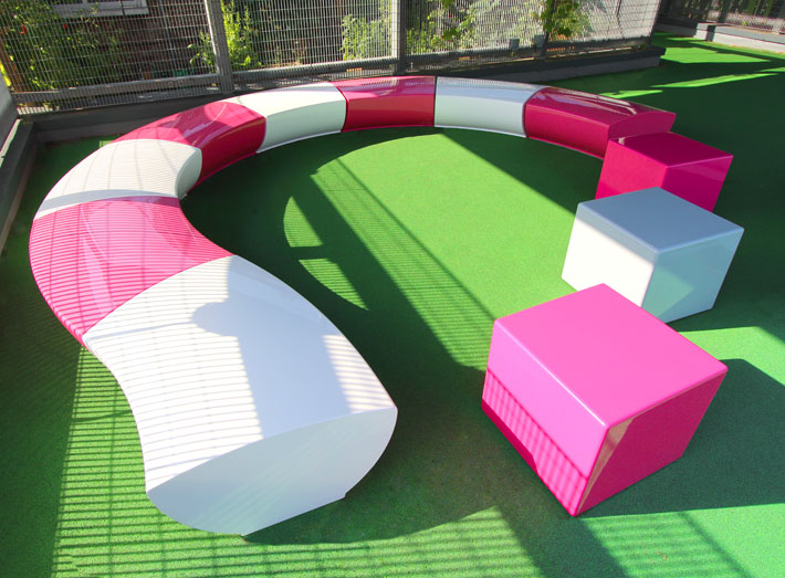 Serpentine seating installation at Earlham Primary School in Stratford, London, created colourful fun spaces for children to engage with their learning and play.