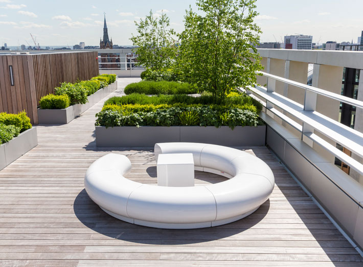 With plants, lawn and extensive decking, the garden now also features a selection of white cubed and curved GeoMet seating.