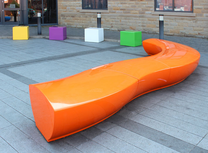 Manufactured in any colour, Serpentine seating with Cube seats add colour and fun for a school playground area.