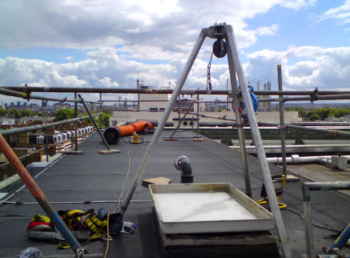 Roof top access view - fibreglass lining of two water storage tanks in Chelsea, London.